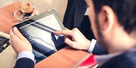 Mann (von hinten aufgenommen) mit Tablet- und Laptop-Computer