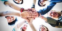 Gruppe junger Menschen stehen lachend im Kreis und legen ihre Hände aufeinander