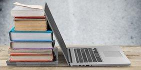 Laptop und Bücherstapel auf einem Tisch