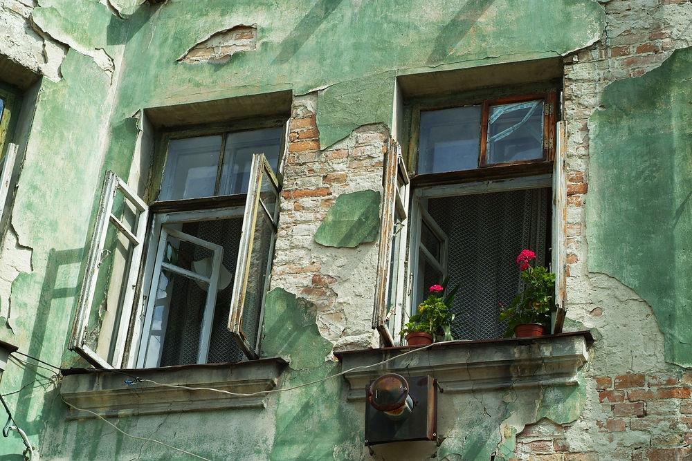 altes grünes Haus mit kaputten Fenstern