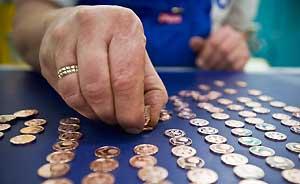 Eine Hand im Vordergrund zählt Cent-Münzen auf blauem Tisch