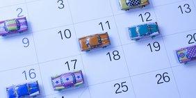 Spielzeugautos stehen auf einem Kalenderblatt