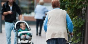 Rentnerin mit Rollator und Kind im Kinderwagen