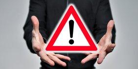 """Hände eines Mannes umfassen ein """"Achtung/Vorsicht""""-Verkehrsschild"""