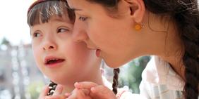 Kind mit Behinderung und Frau (Erzieherin / Pädagogin)