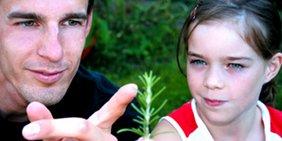 Erwachsener zeigt einem Kind eine Pflanze