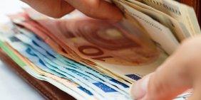 Hand an offener Geldbörse mit Euro-Scheinen