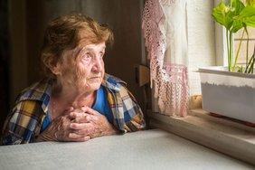 Ältere Frau sitzt am Fenster