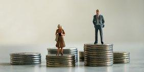 Miniatur-Frau steht auf niedrigem Stapel Münzen, Minitaur-Mann auf hohem