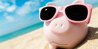 Sparschwein mit Sonnenbrille am Strand