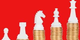 Schachfiguren auf Münzstapeln - Einkommensungleichheit