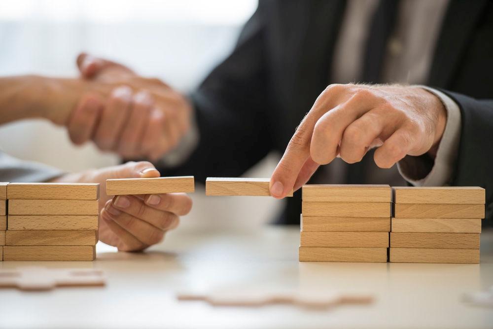 Brücken bauen mit Bausteinen zwei Hände business