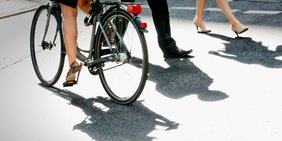 Fußgänger und Fahrrad mit Schatten