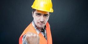 Bauarbeiter mit Helm zeigt Faust
