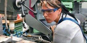 Junge Frau mit Schutzbrille an CNC-Fräse