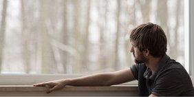 Trauriger junger Mann schaut aus dem Fenster